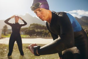Focused young man checking his watch while in wetsuit at the lake. Man looking at watch after practice run. Triathletes getting ready for race.